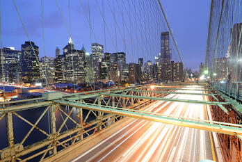 View of downtown Manhattan from the Brooklyn Bridge with traffic flying by.-1